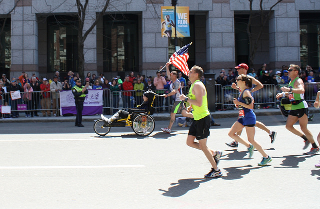 A flag wielding runner pushing another marathon participant in a wheelchair leads a pack rounding out their 26th mile at the Boston Marathon. By Zoe Lake