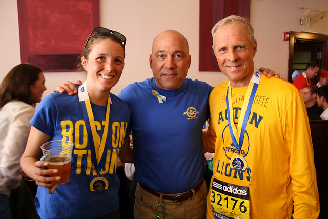 Emily Zimmerman poses with bar owner Tony Castagnozzi, and fellow marathoner Dave Christmas at The Rattlesnake Bar and Grill on Boylston following the 118th Boston Marathon. By Zoe Lake.